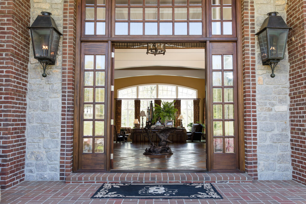 Exterior entryway with stone, brick, and gas lanterns, Eric Ross of Nashville interior design firm, Eric Ross Interiors, was the designer and decorator for this home.